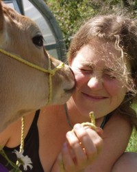 Our dear Molly (who apprenticed here in 2004) was especially gracious about receiving cow kisses. (photo by Michael Phillips)